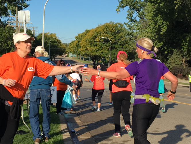 Volunteer handing out water to runners