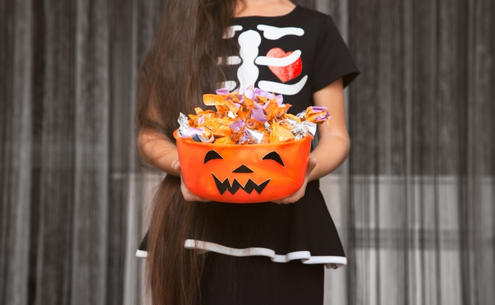 Little girl is holding a scary bowl with candies